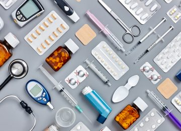 Directly above flat lay flat lay shot of various medical supplies. Full frame shot of medicines placed with syringes and diagnostic tools. All are on gray background.  Knolling concept.
